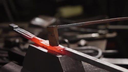Smith macht Schnitte auf einem beheizten Eisen