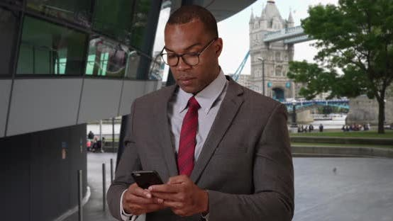 African-American professional in London poses proudly after checking phone