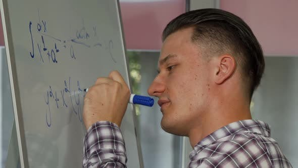 Thumbnail for Handsome Young Man Solving Math Problem on Whiteboard