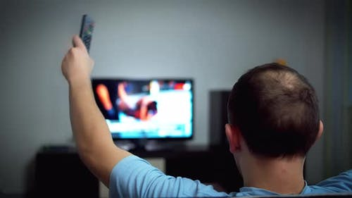 A Man Watches a Fight on TV Worries Waves His Hands Strong Emotions Rear View
