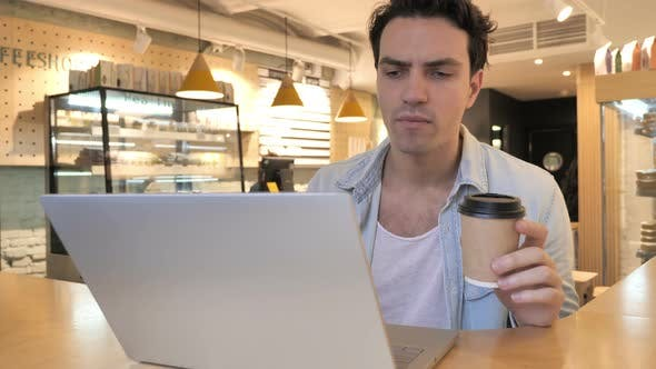Cover Image for Young Man Drinking Coffee and Working on Laptop in Cafe