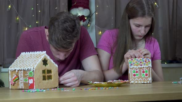 Thumbnail for A Guy and a Girl Decorate a Christmas Gingerbread House