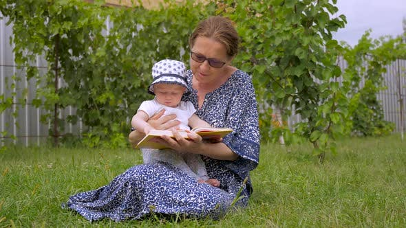Thumbnail for Ladies Reading Book. Grandmother with Granddaughter Sitiing on Green Grass. Baby Girl with Nanny