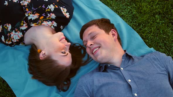 Thumbnail for Happy Young Adult Couple Lying on the Grass Over Sunset