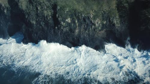 Artistic Blue Coastal Background Aerial Of Slow Motion Waves Crashing Rock Cliff