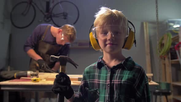 Thumbnail for Boy in Glasses Stands with Hammer and Looks at the Camera