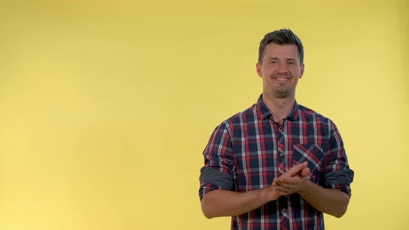 Thumbnail for Portrait of Smiling Young Man Giving Applause To Somebody on Yellow Background