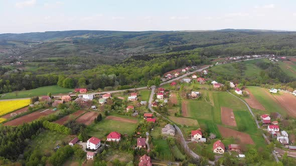 Thumbnail for Aerial Drone View of Green Fields, Hills and Trees in a Village with Small Houses, Poland