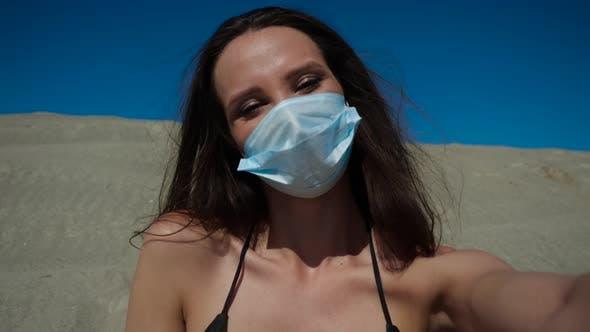 Ein Mädchen in einer medizinischen Maske während eines Coronavirus am Strand. Pandemie 2020.