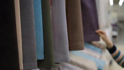 Customer Choosing Fabric for Curtains in a Store