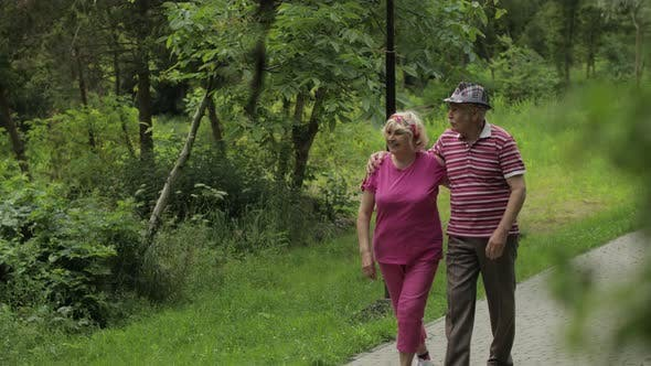 Senior Caucasian Couple Walking in Park Embracing. Elderly Man Walks with Woman. Husband, Wife