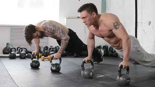 Anstrengendes Crossfit-Workout. Zwei junge Athleten trainieren aktiv. Pushups auf Dumbell