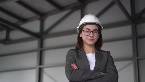 A Young Woman in a Protective Helmet Crossed Her Arms and Stands at a Construction Site. The Boss