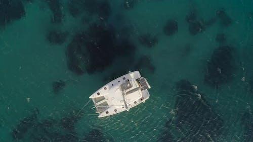 Aerial view of a catamaran anchored in Aegean sea, Greece.