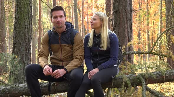 Thumbnail for A Hiking Couple Sits on a Broken Tree and Talks in a Forest