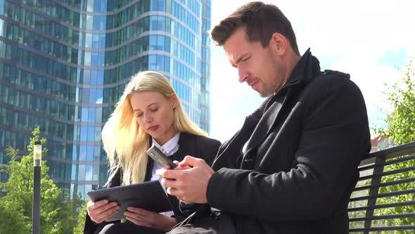 Thumbnail for A Businessman and a Businesswoman Work on a Smartphone and a Tablet and Talk in an Urban Area