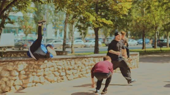 Young Guys Run Through the Park and Do a Somersault with a Coup Parkour