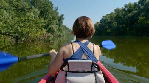 Woman Swims on a Kayak on a Calm River