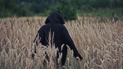 Scary witch evil outdoors. Back view on scary ghost in black robe and hood
