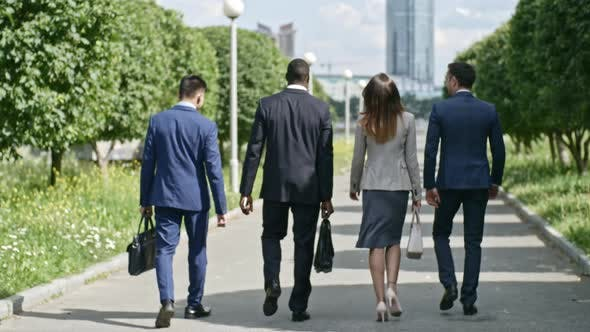 Thumbnail for Business Partners Walking Along Avenue at Summer Day