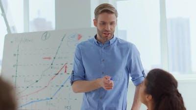 Team Leader Talking Colleague Indoors