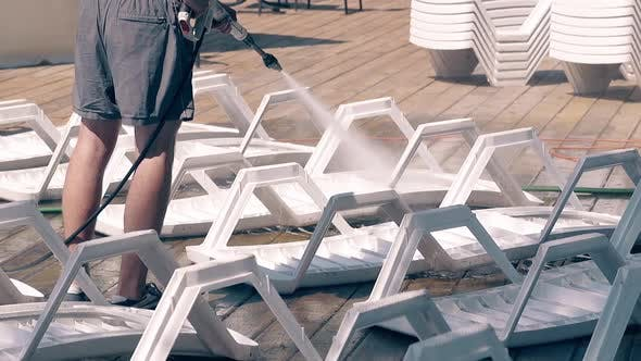Beach Worker Washes the Beach Loungers