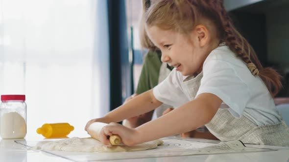 Thumbnail for Girl in Apron Rolls Dough Cooking with Mother at Table