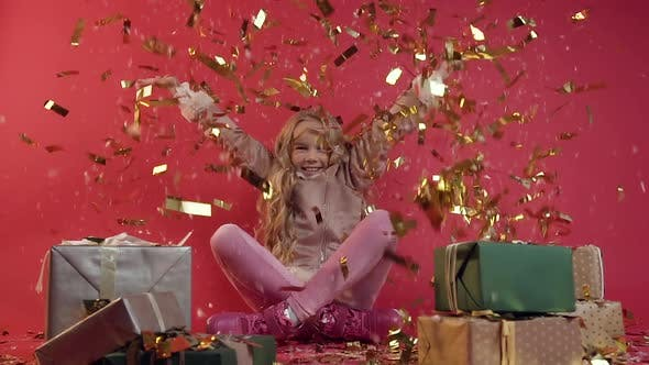 Thumbnail for Smiling Teen Girl with Long Hair Sitting on the Floor Among Colourful Gifts Under Confetti Rain