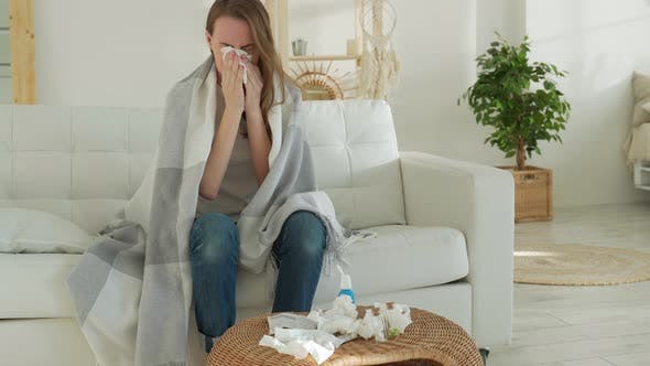 Woman Wrapped in a Blanket Feels Sick with a Cold and Fever at Home Sick with the Flu Sitting on the