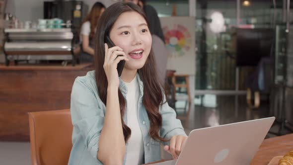 Young Asian freelance female work talk on phone with customer at coffee shop.