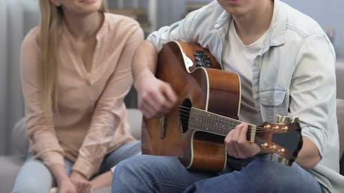 Cute Teenager Male Playing Guitar at College Part, Girl Listening, First Love