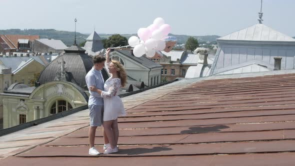 Thumbnail for Couple standing on a rooftop and holding balloons