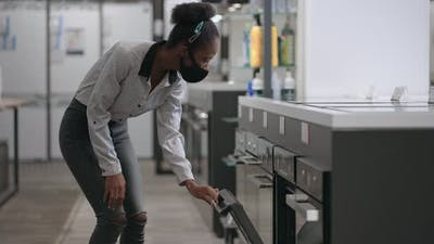 Afroamerican Woman is Shopping in Home Appliances Store Black Lady is Choosing Equipment for Home