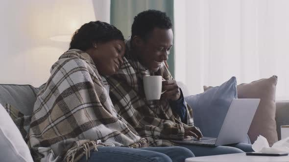 Young Sick African American Man and Woman Watching Movie or Funny Videos Online on Laptop Sitting