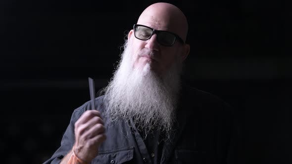 Thumbnail for Portrait Of Bald Man Brushing Gray Beard With Comb Outdoors At Night