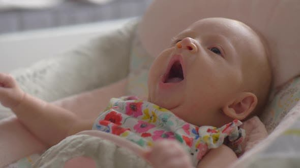 Thumbnail for Baby Girl of Two Months Lying in Bouncy Seat and Yawning