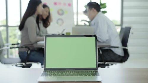 Laptop computer with green screen on table in office
