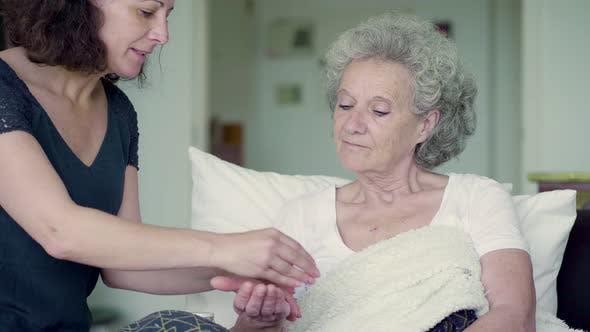 Thumbnail for Smiling Nurse Giving Pills To Senior Woman at Home