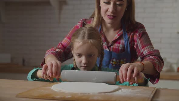 Mom Teaching Child Rolling Pastry with Rolling Pin