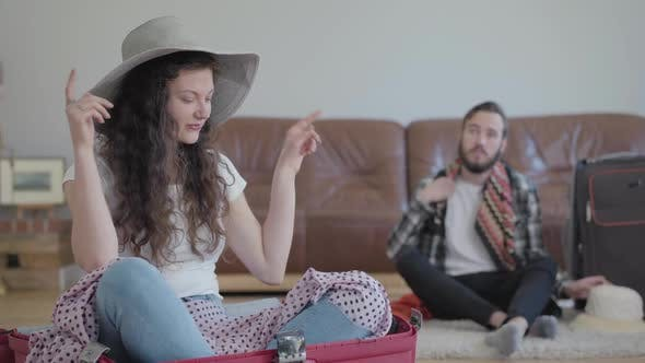 Thumbnail for Happy Man and Woman on the Floor at Home Packing a Suitcase Before Travel