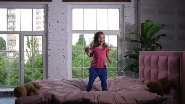 Thumbnail for Happy Little Child Jumping on Cozy Bed in Bedroom