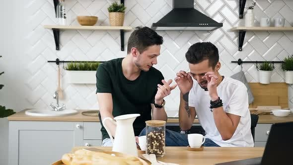 Thumbnail for Gay Handsome Men are Sitting Behind the Kitchen Table Something Talking for During Drinking Coffee