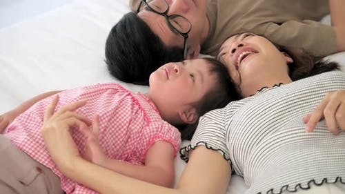 Happy family with mother, father and disabled daughter spending time together at home.