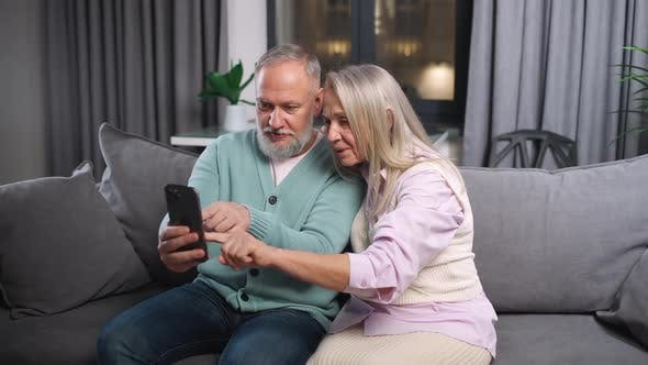 Elderly Couple View Photos on a Smartphone Sitting on the Sofa in Living Room Positive Emotions