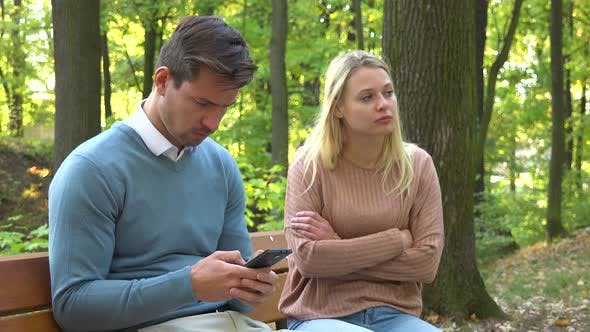 Thumbnail for A Man and a Woman Sit in a Park, the Man Is Absorbed with His Smartphone, the Woman Is Angry at Him