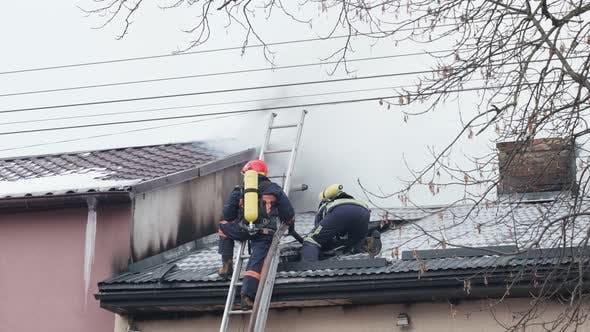 Firemen Extinguish Fire on Burntout Roof