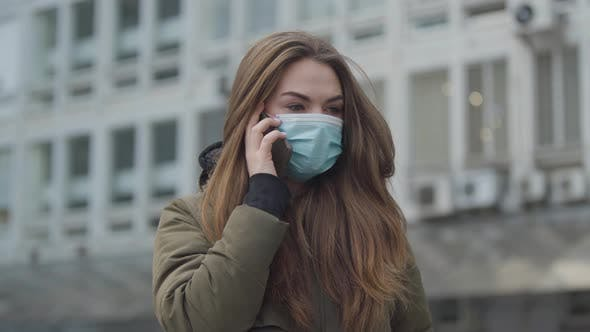 Cover Image for Young Beautiful Woman in Protective Mask Standing in City and Talking on the Phone