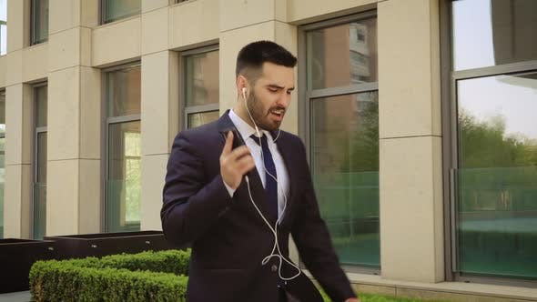 Thumbnail for Happy Successful Businessman Dancing In Wireless Earphones