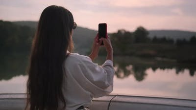 Woman Taking Photos of Picturesque River at Sunset