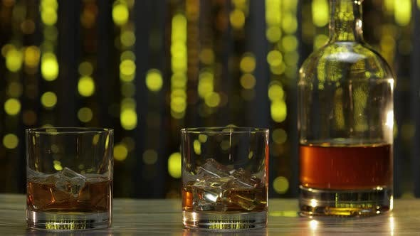 Thumbnail for Barman Pushes, Puts Two Glasses with Golden Whiskey, Cognac or Brandy with Ice Cubes on Wooden Table
